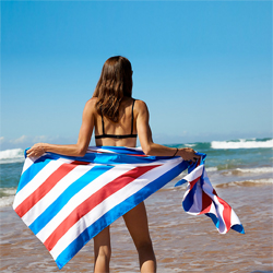 A woman on the beach in a bikini, holding up a blue and red striped towel