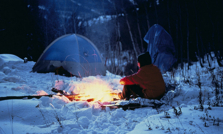 A person sat in the snow with a campfire infront of them, and a tent in the background