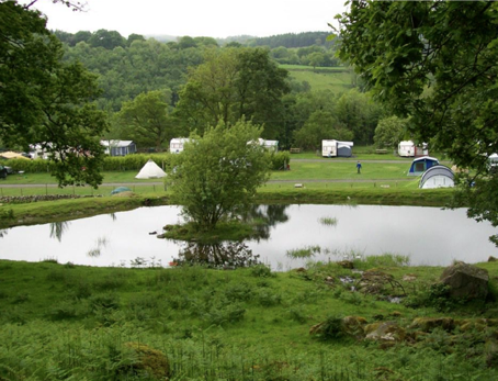 A green field with a large lake in the middle. Across from the lake there are some tents