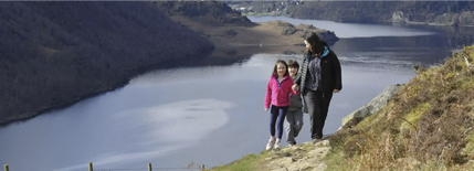 A woman and two children walking along a path on a mountain, and there is a lake in the background