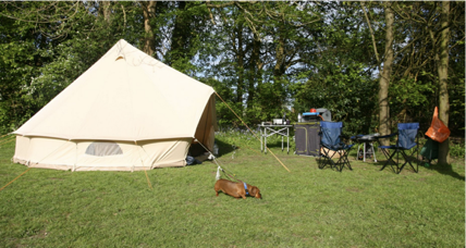 A beige glamping tent in a green field with camping equipment next to it