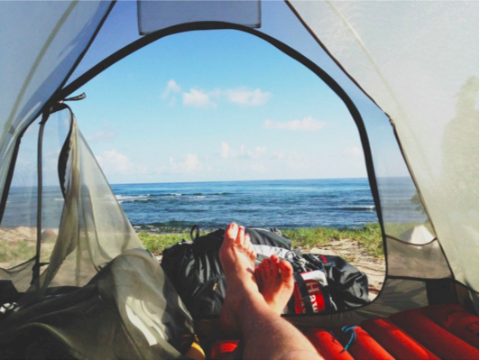 This image has been taken by someone lying down in a tent, showing the view outside the tent door, looking out at a line of grass and then the blue sea.