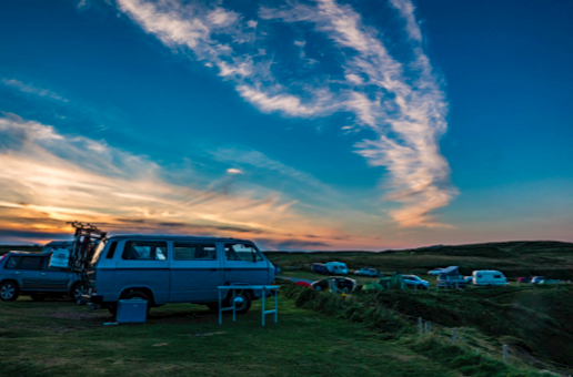 An old looking campervan overlooking a campsite with other camping vehicles, in a field.