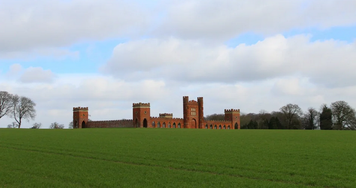 A large, green field with blue sky. There is a very large orange brick castle-type bulding in the field.