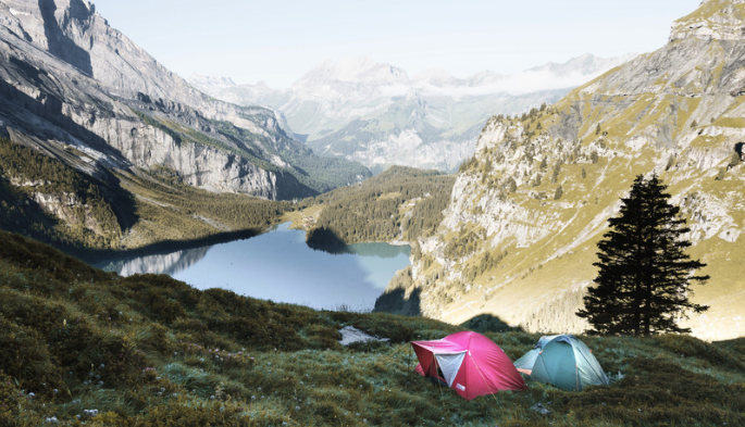A red and blue tent, pitched by a beautiful blue lake which is surrounded by rocky mountains and trees.