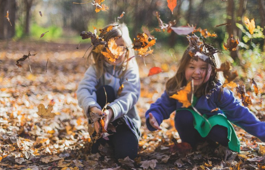 Two young girls throwing autumn leaves from the ground