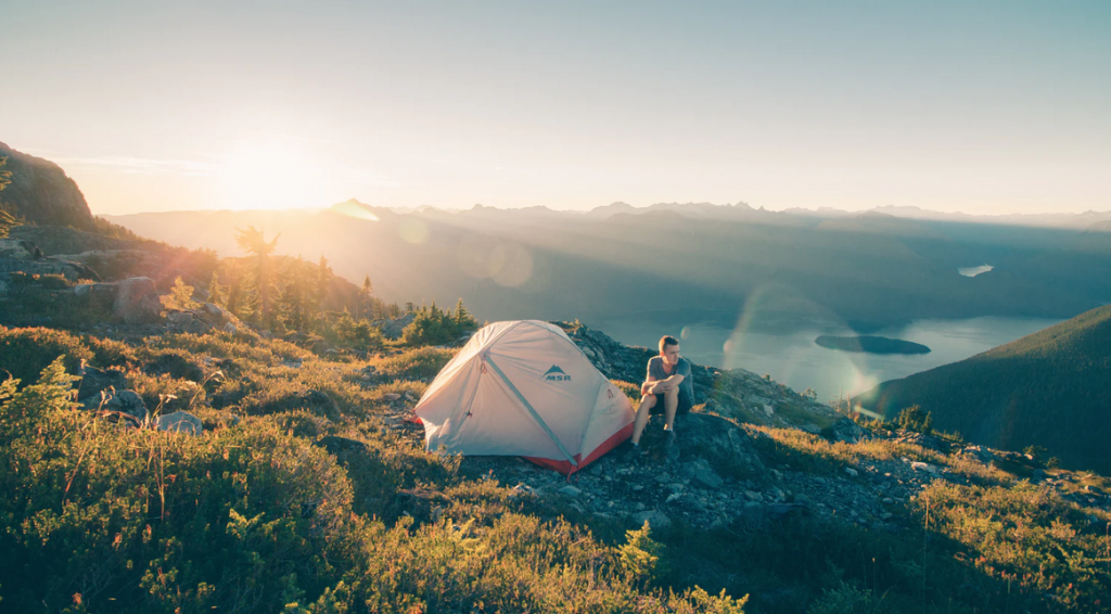 A man sat with his tent on a sunny mountain