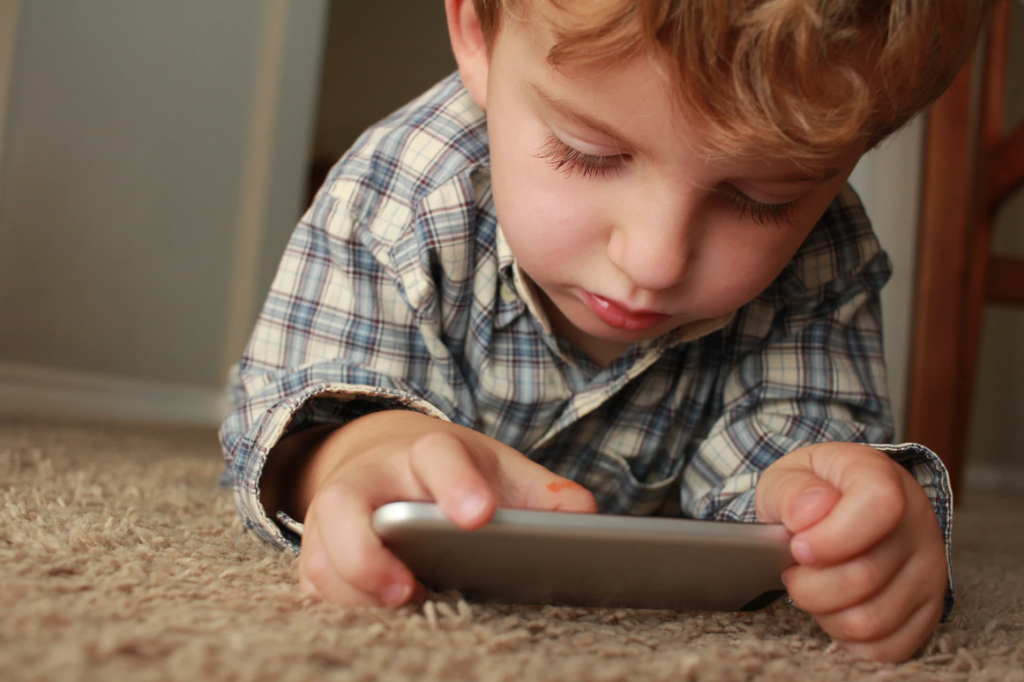 A boy laying on the carpet looking at an ipad