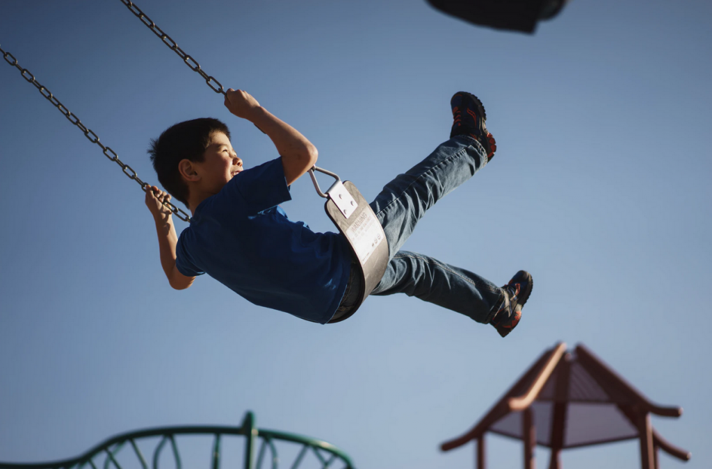 A young boy on a swing with his legs in the air
