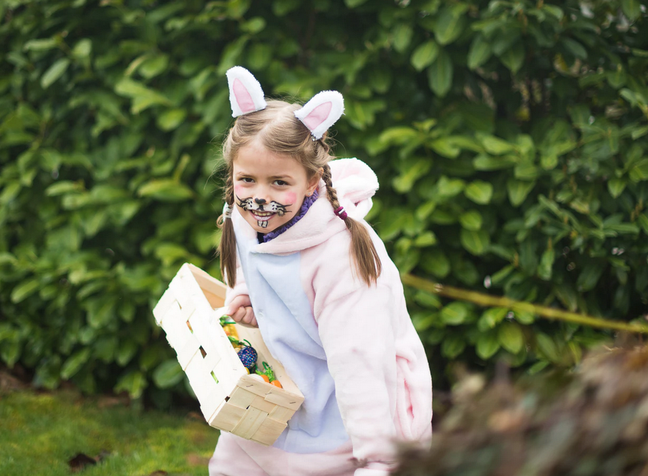 girl wearing rabbit ears carrying a tray of easter eggs