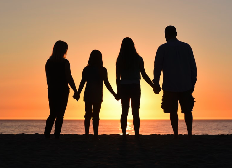 Four people stood in a sunset holding hands
