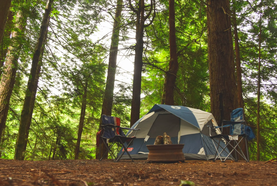 A blue tent in the woods with two camping chairs infront of it.