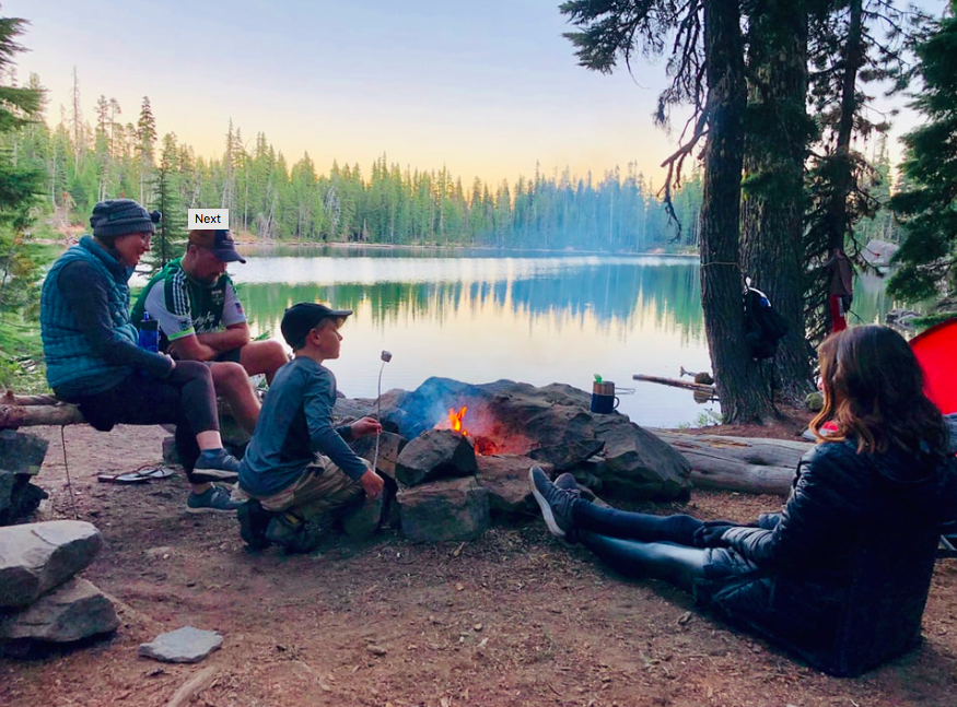 A family group sat around a campfire holding marshmallows on sticks.