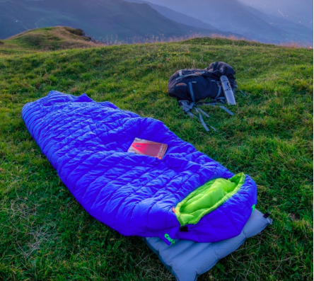 A blue sleeping bag and backpack on the grass.
