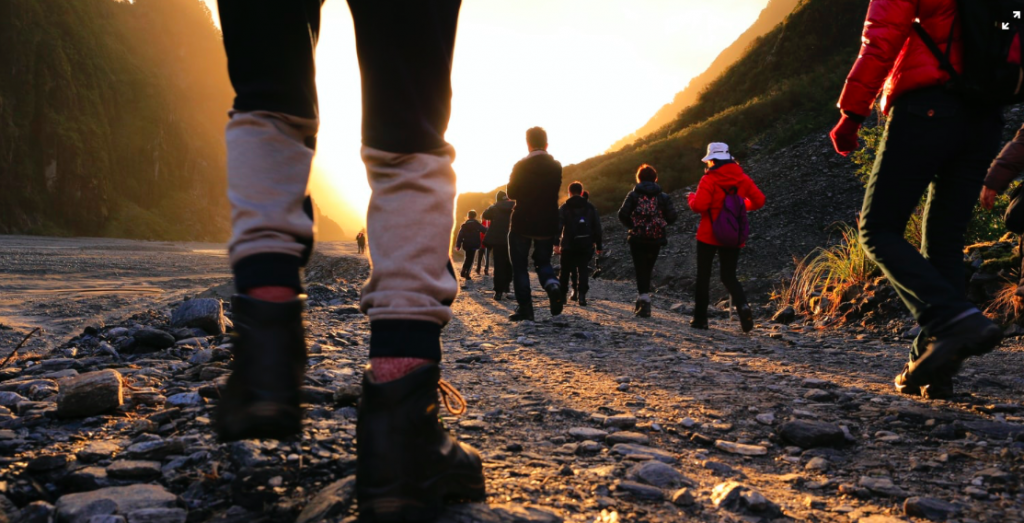A group of people in hiking gear walking along a rocky path