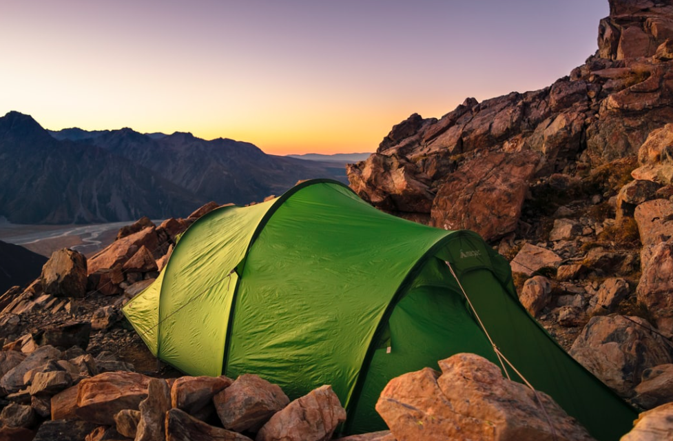 A green tent set up in a rocky mountain