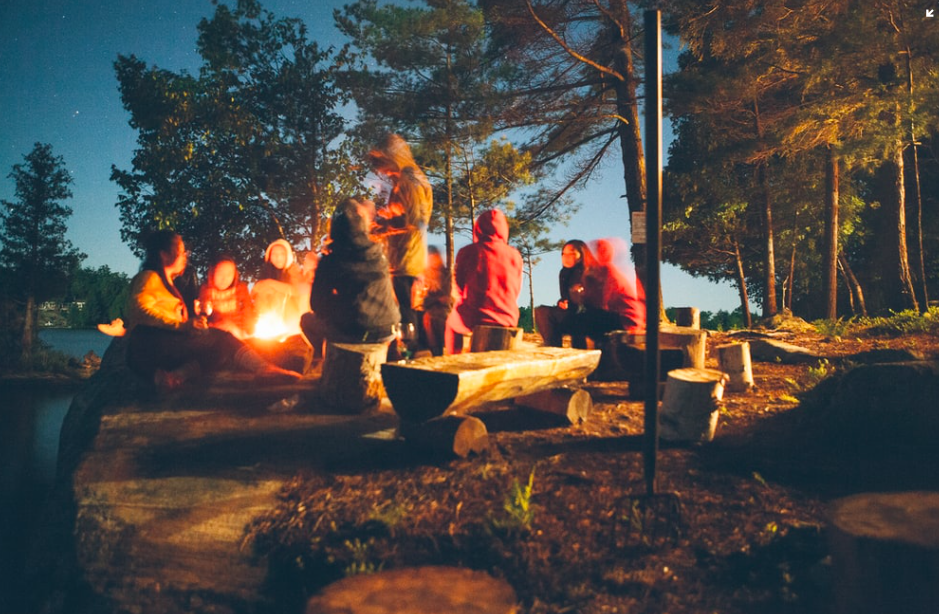 A group of people sitting around a campfire together