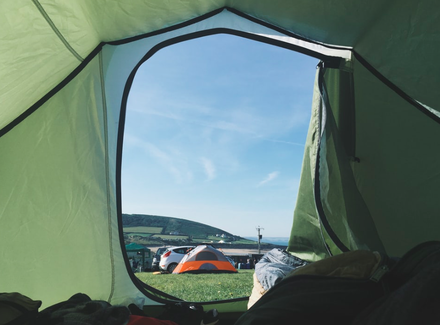 The view from inside a green tent, looking out at a blue sky