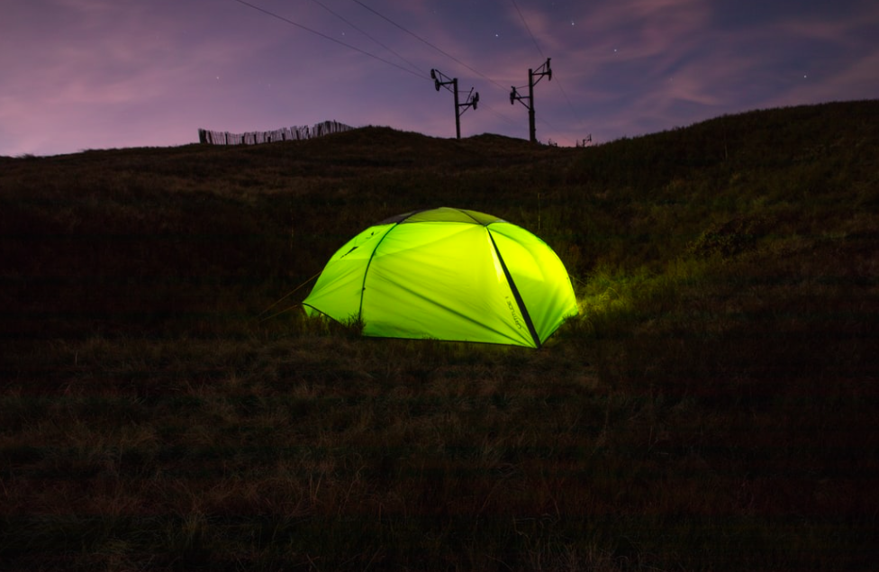 A lit up green tent at night time