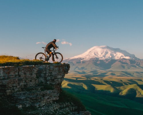A man on a bike looking at the view over a mountain