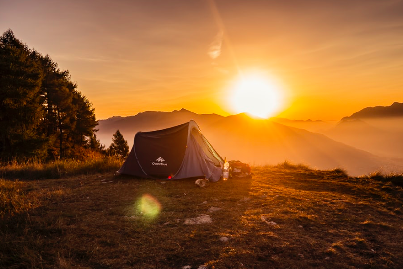 A quechua tent on the grass with an orange sunrise