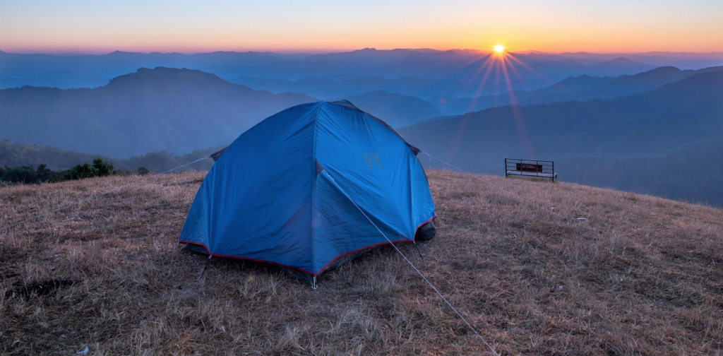 A small tent on a mountain edge with the sunset in the distance