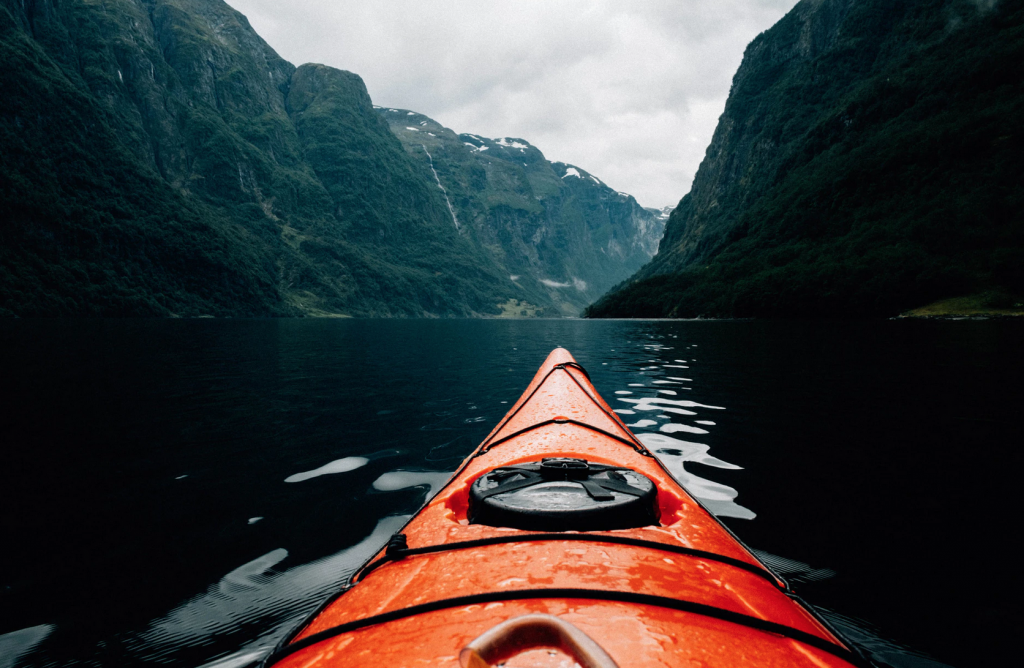 The end of an orange kayak in water surrounded by mountains