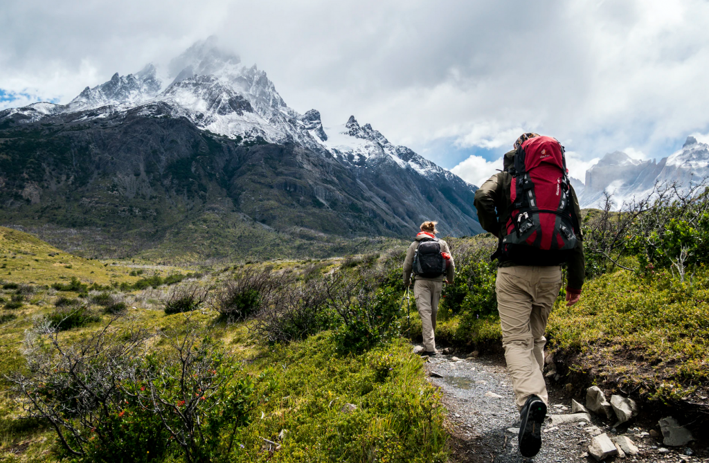 Two people with backpacks walking along a grassy path towards mountains