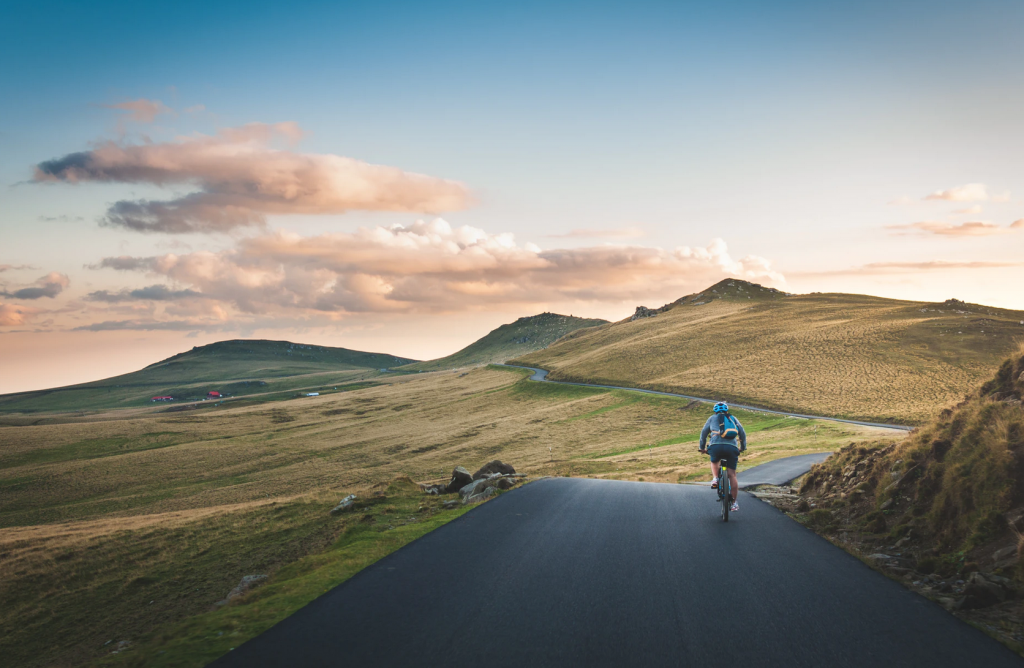 A person cycling along a road surrounded by green fields and hills