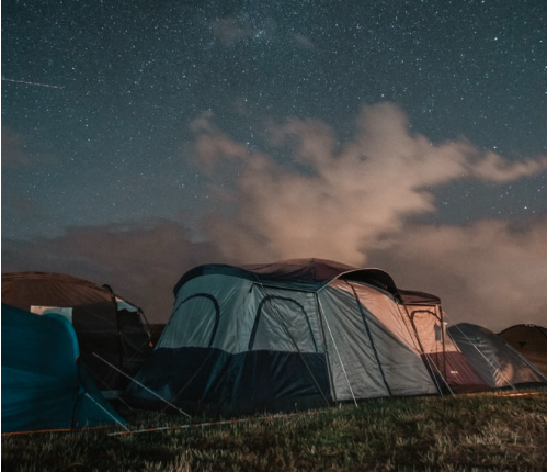 A grey tent on grass with a starry sky behind it