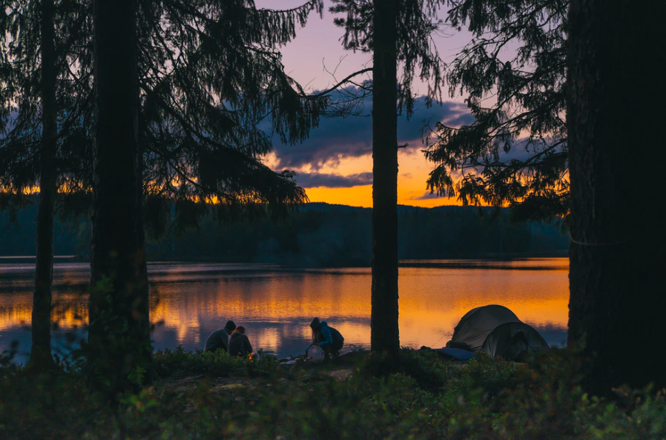 Three people sitting by a lake with their tent next to them during sunset
