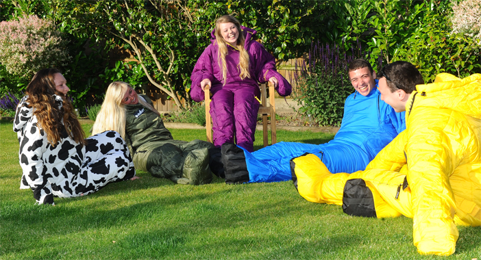 Friends sat outside wearing Sleeping Bag Suits
